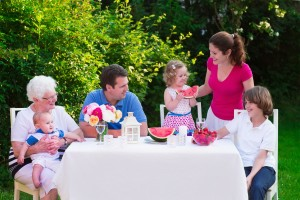 Big family with children have lunch outdoors. Parents with 3 kids and grandmother eat in the garden. Picnic for mother, father, baby boy, toddler girl and teenager child. Generations and retirement.